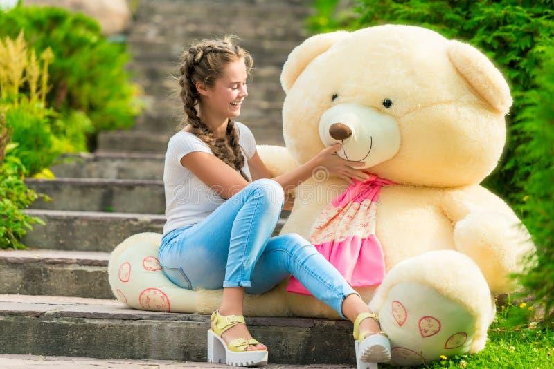 Schönes junges Mädchen mit einem enormen Teddybären lizenzfreies stockbild