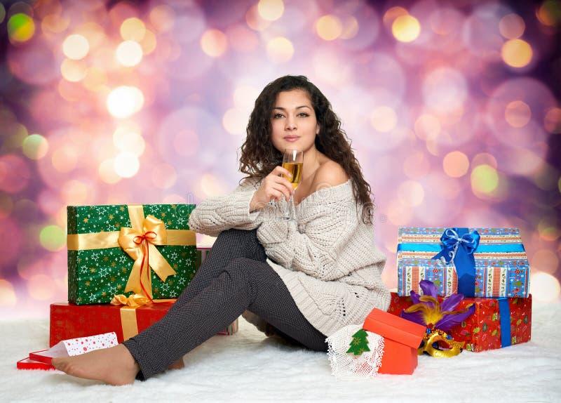 Schönes junges Mädchen mit einem Glas Champagner und Geschenkboxen lizenzfreie stockfotografie