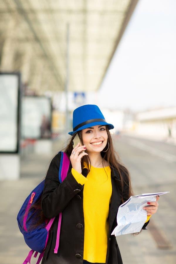 Schönes junges Mädchen mit einem Rucksack und einem blauen Hut, sprechend auf Mobile in der Straße nahe dem Flughafen stockfotos