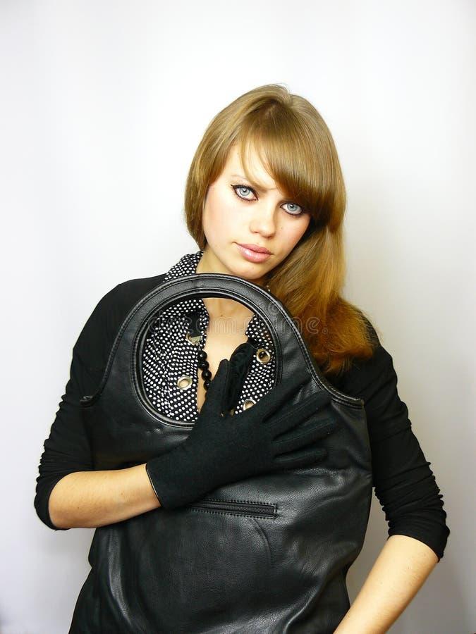 Schönes junges Mädchen mit einem schwarzen ledernen Beutel lizenzfreies stockbild