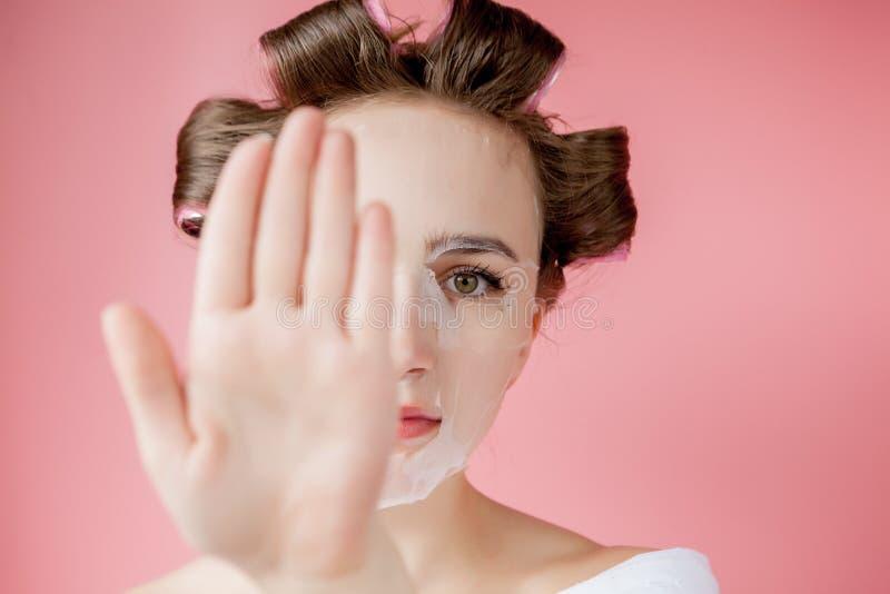 Schönes junges Mädchen mit einer Maske und Lockenwicklern, die ihr Gesicht berühren stockfotos
