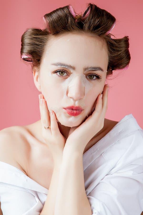 Schönes junges Mädchen mit einer Maske und Lockenwicklern, die ihr Gesicht berühren stockbilder