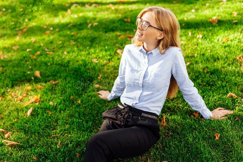 Schönes junges Mädchen mit Gläsern lächelnd und die Hitze genießend, die auf dem grünen Rasen sitzt stockfotos