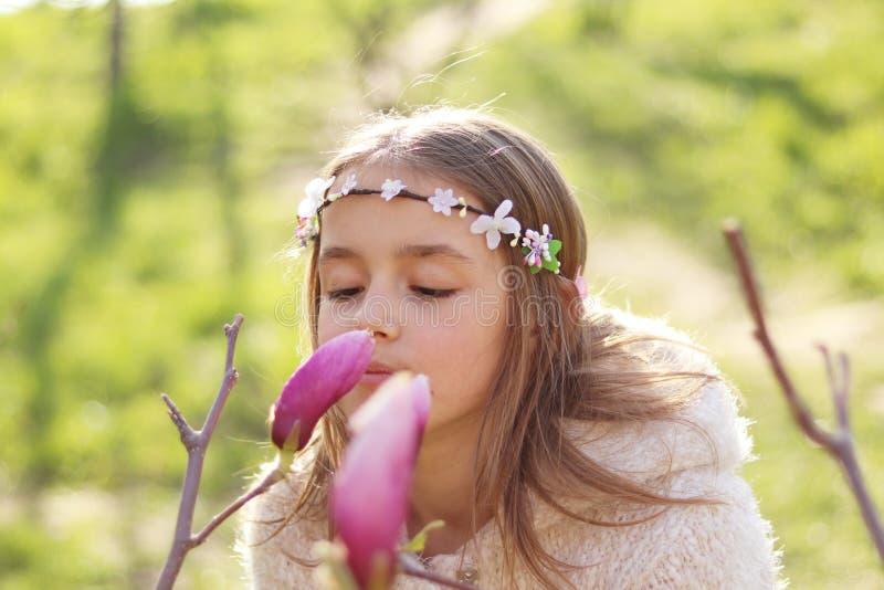 Schönes junges Mädchen mit handgemachtem Haarkranz auf ihrem Kopf, der Magnolienblume betrachtet und sie Aroma riecht stockbild