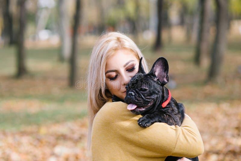 Schönes junges Mädchen mit ihrem Hund im Herbstpark stockfotografie
