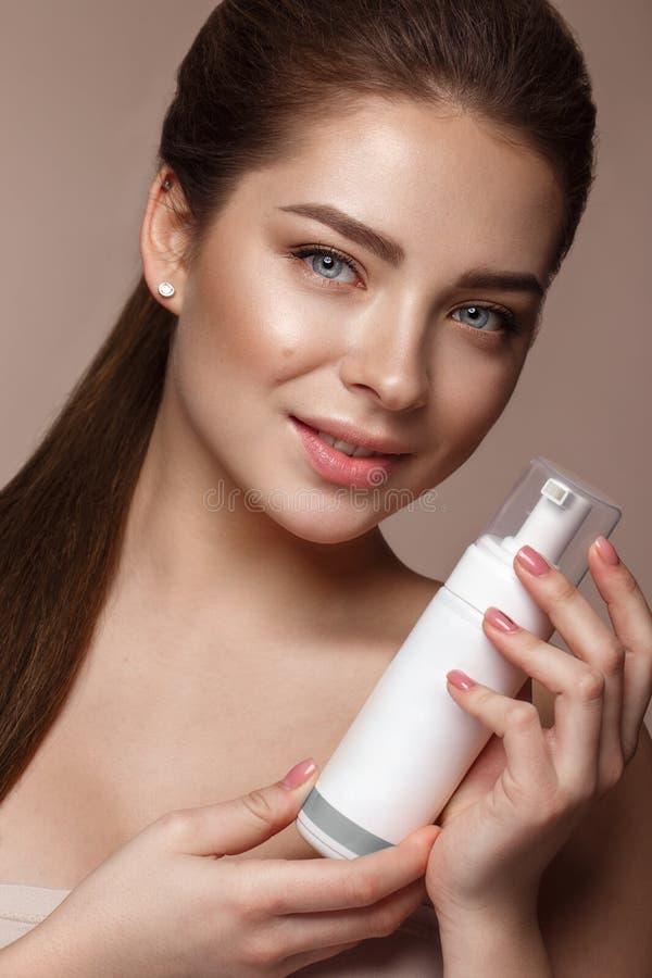 Schönes junges Mädchen mit natürlichem nacktem Make-up mit Kosmetik in den Händen Schönes lächelndes Mädchen lizenzfreie stockbilder