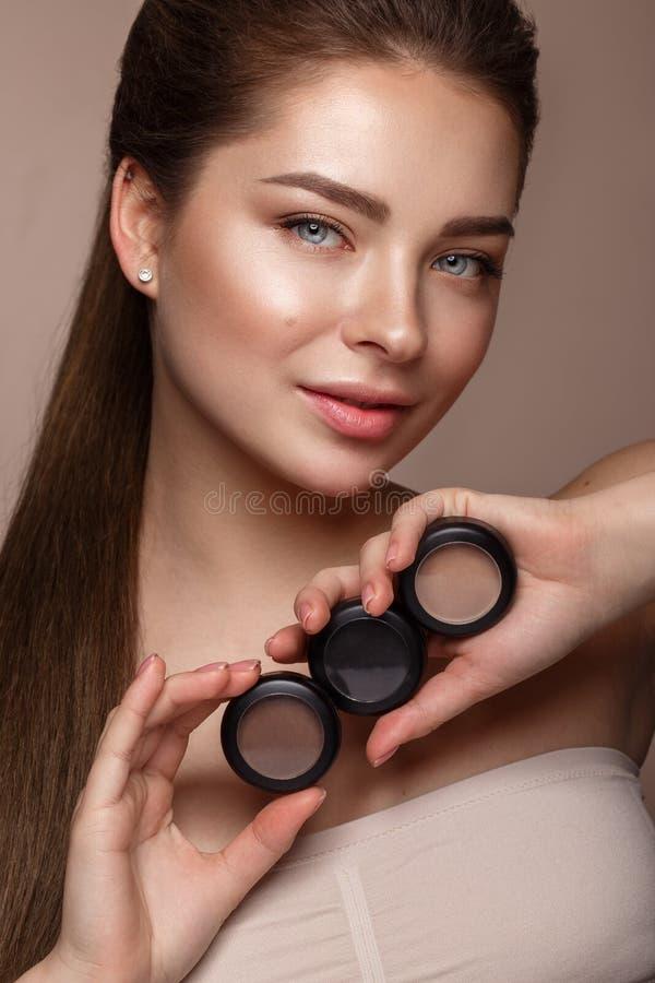 Schönes junges Mädchen mit natürlichem nacktem Make-up mit Kosmetik in den Händen Schönes lächelndes Mädchen stockfotografie