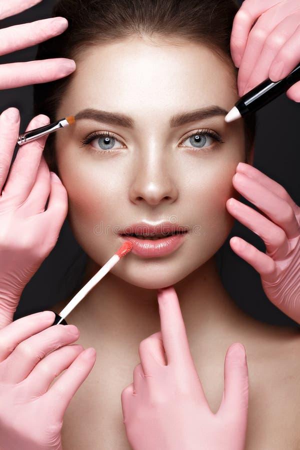 Schönes junges Mädchen mit natürlichem nacktem Make-up mit kosmetischen Werkzeugen in den Händen Schönes lächelndes Mädchen stockfotografie