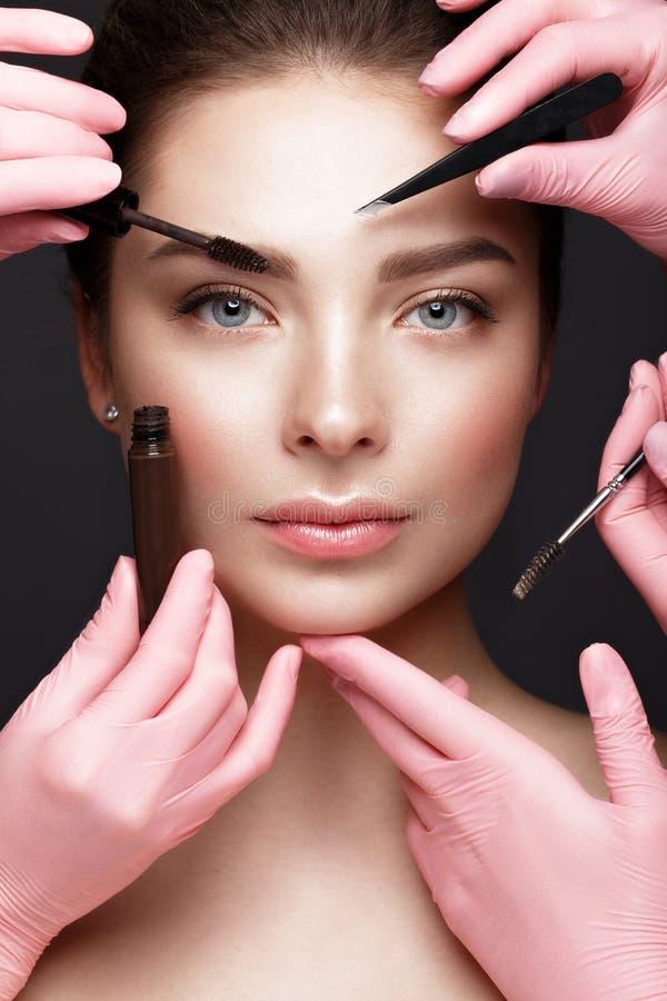 Schönes junges Mädchen mit natürlichem nacktem Make-up mit kosmetischen Werkzeugen in den Händen Schönes lächelndes Mädchen lizenzfreie stockbilder