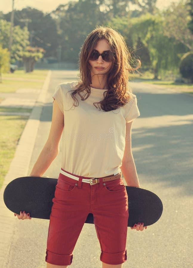 Schönes junges Mädchen mit Skateboard lizenzfreie stockbilder