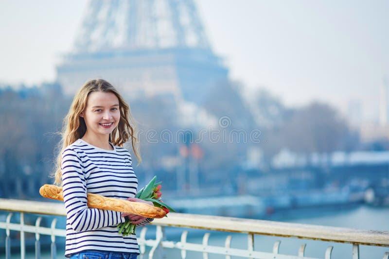 Schönes junges Mädchen mit Stangenbrot und Tulpen nahe dem Eiffelturm lizenzfreie stockfotografie