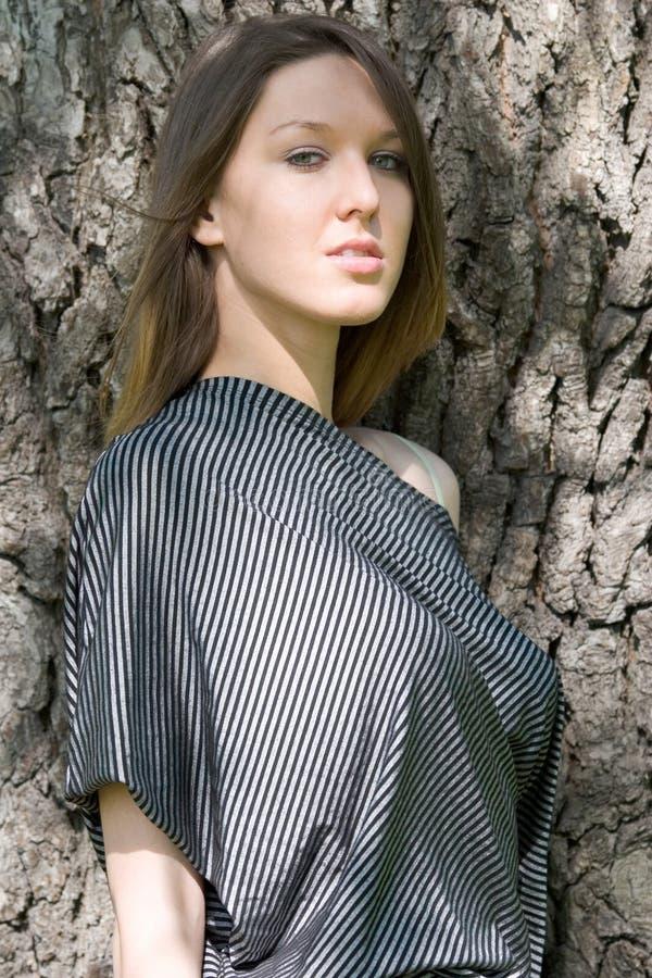 Schönes junges Mädchen nahe Baum lizenzfreies stockfoto