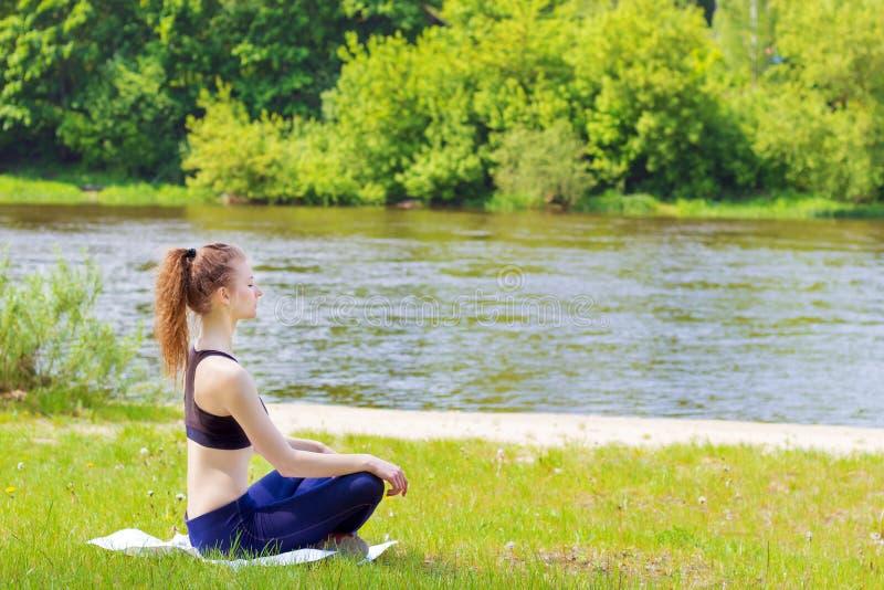 Schönes junges Mädchen nimmt an Sport, Yoga, Eignung auf dem Strand durch den Fluss an einem sonnigen Sommertag teil stockbild