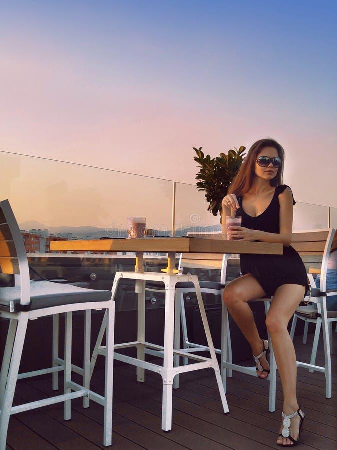 Schönes junges Mädchen sitzen bei Tisch im Café bei Sonnenuntergang weiches warmes c lizenzfreies stockbild