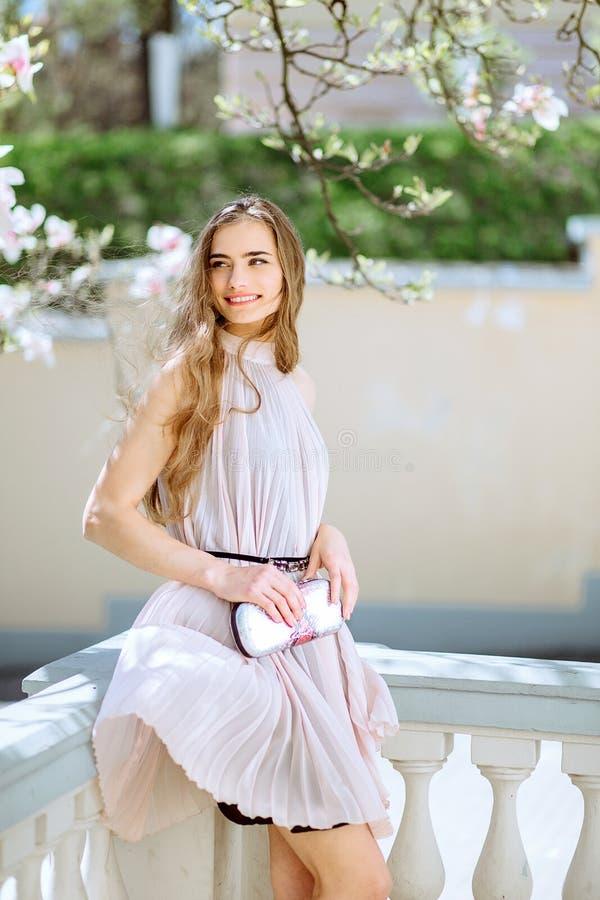 Schönes junges Mädchen steht unter den blühenden Bäumen Weiße Blumen Frühlings-Mädchen mit ihrem Haar in einem beige Kleid stockbild