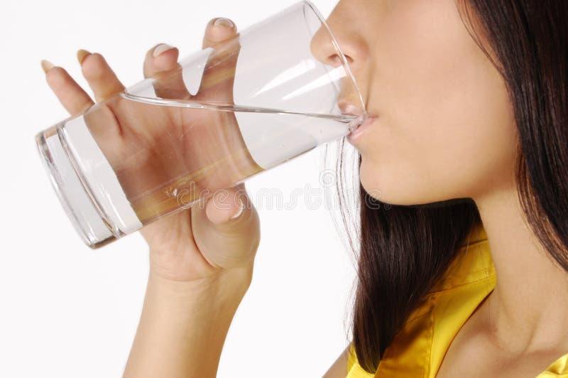 Schönes junges Mädchen trinkt Wasser vom Glas lizenzfreies stockbild