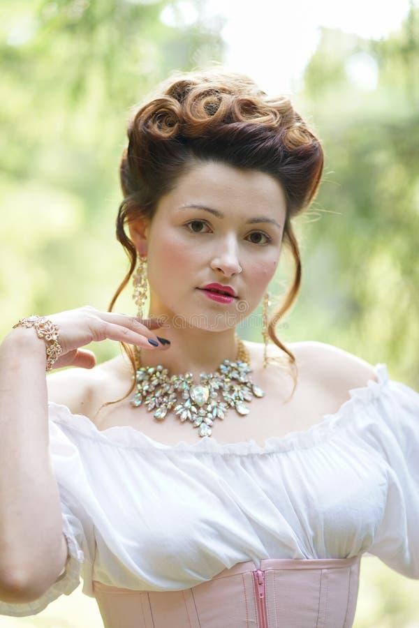 Schönes junges molliges Mädchen, das im mittelalterlichen Retro- Korsett und in der weißen Weinlesewäsche im Wald aufwirft lizenzfreie stockfotografie