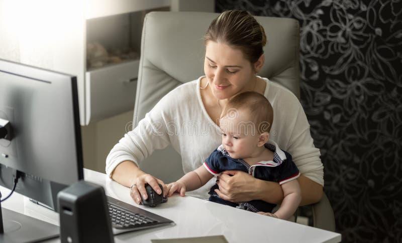 Schönes junges owman, das im Büro arbeitet und ihr entzückendes einjähriges Baby hält lizenzfreie stockfotos