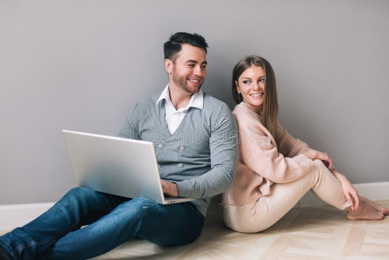 Schönes junges Paar benutzt einen Laptop und lächelt beim Sitzen auf dem Boden lizenzfreies stockfoto