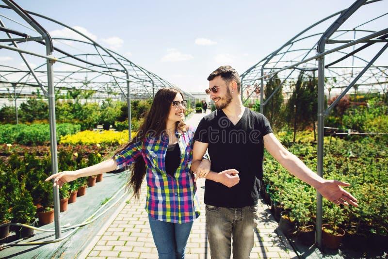 Schönes junges Paar in der zufälligen Kleidung wählt Anlagen und lächelt während Stellung im Gewächshaus lizenzfreie stockbilder