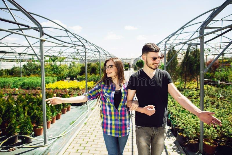 Schönes junges Paar in der zufälligen Kleidung wählt Anlagen und lächelt während Stellung im Gewächshaus lizenzfreies stockbild