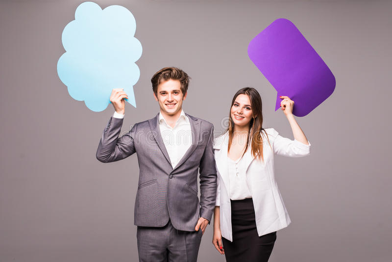 Schönes junges Paar hält Spracheblasen, betrachtet Kamera und lächelt, auf Grau lizenzfreie stockfotos