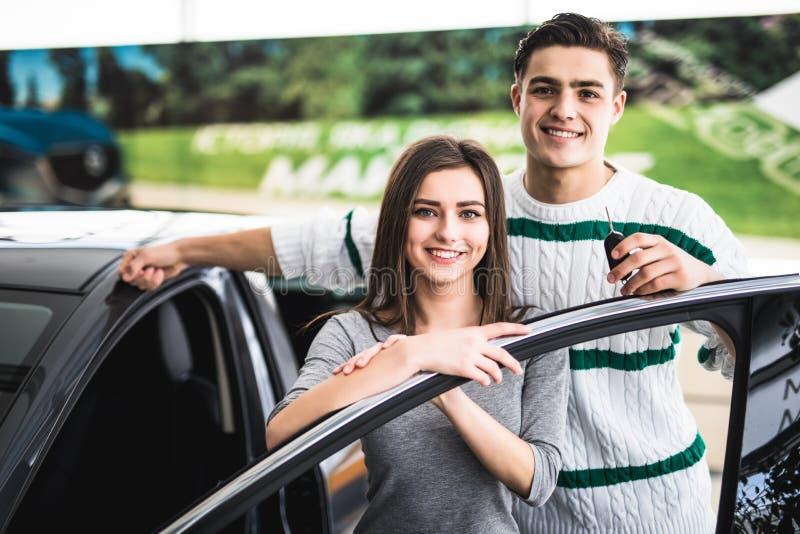 Schönes junges Paar ist, betrachtend lächelnd und Kamera beim Lehnen auf ihrem Neuwagen in einer Autoausstellung Mann hält Autosc lizenzfreies stockfoto