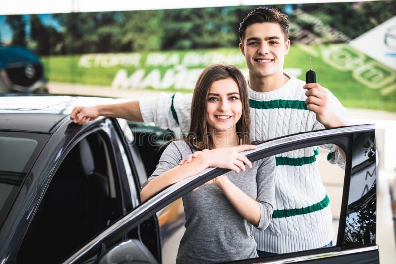 Schönes junges Paar ist, betrachtend lächelnd und Kamera beim Lehnen auf ihrem Neuwagen in einer Autoausstellung Mann hält Autosc stockfotografie
