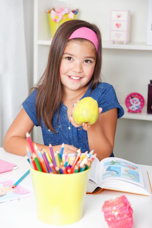 Schönes junges Schulmädchen, das einen Apfel anbietet stockfotografie