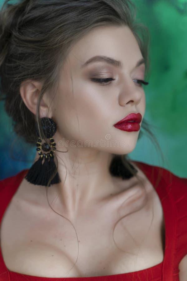 Schönes junges sexy elegantes Mädchen mit den großen Brüsten, ein rotes festes Kleid und Ohrringe tragend, die sinnlich auf einem lizenzfreie stockfotos