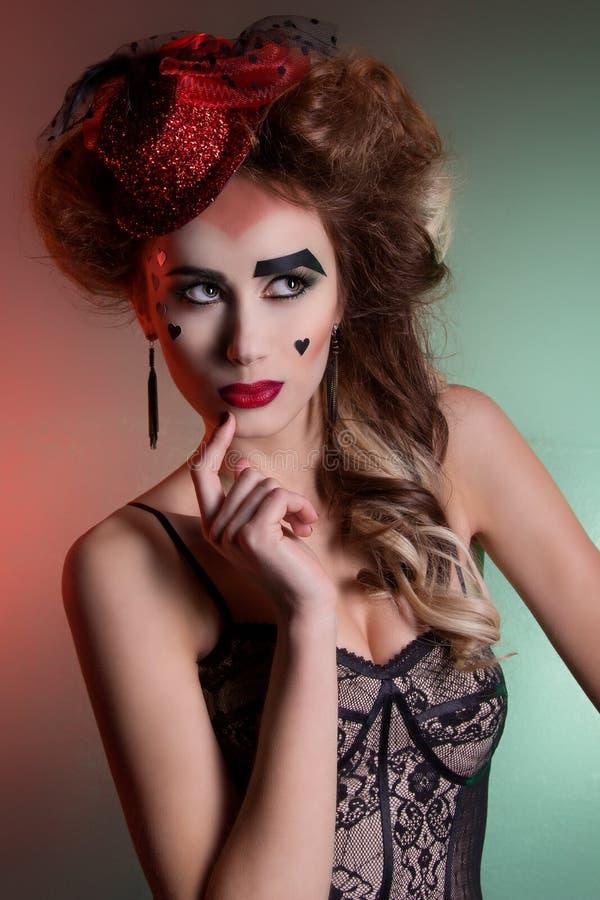 Schönes junges sexy Mädchen mit dem üppigen Haar im theatralischen Retro- Blick mit rotem Hut in ihrem hellen Make-up des Haares  stockfoto