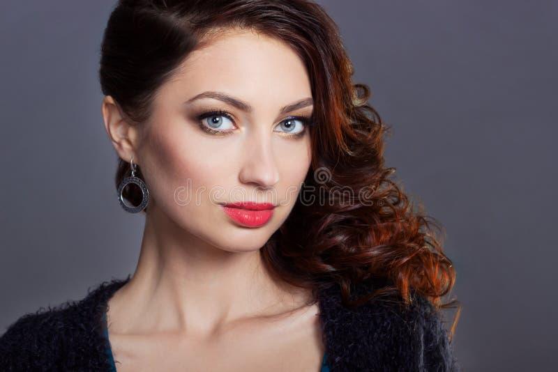 Schönes junges sexy Mädchen mit Locken mit hellem festlichem Make-up, pralle Lippen das Bild zum neuen Jahr, am Weihnachtsabend lizenzfreies stockfoto