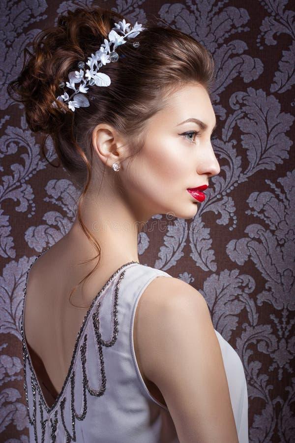 Schönes junges sexy süßes Mädchen mit den großen roten Lippen in heiratendem weißem Kranz auf dem Kopf mit schöner Hochzeitsfrisu stockfotografie