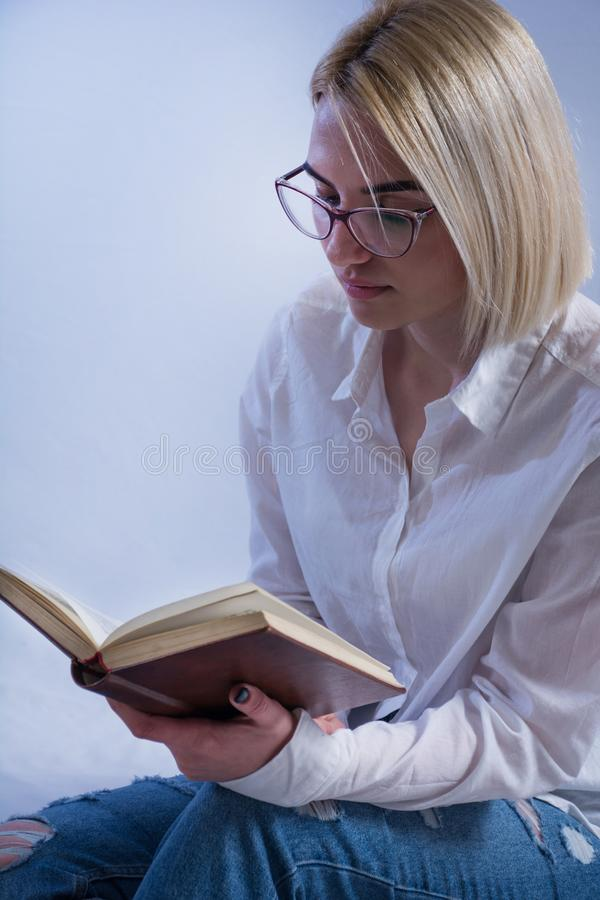 Schönes junges Studentenmädchen, das altes Buch mit Gläsern liest stockfoto