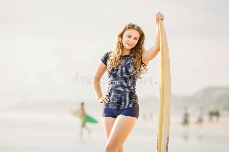 Schönes junges Surfermädchen bleibt auf dem Strand an stockbilder