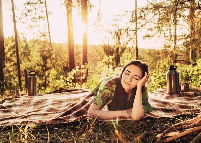Schönes junges träumendes Mädchen, das auf einem Plaid in einer Waldlichtung während des hellen Sonnenlichts des Sonnenuntergangs lizenzfreies stockbild