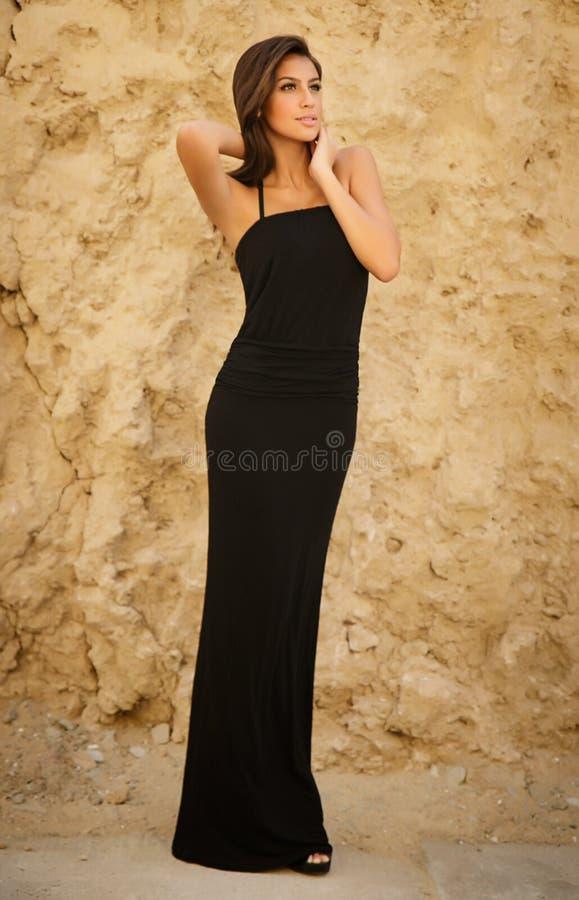 Schönes junges vorbildliches Mädchen im schwarzen Kleid, Sandwand stockfotos