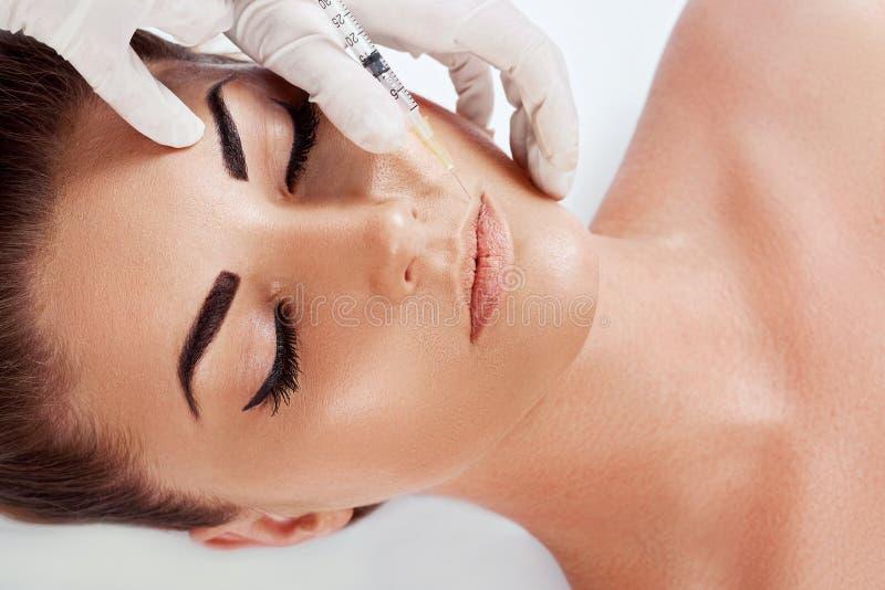 Schönes junges weibliches Gesicht und Hände in den Handschuhen mit der Schönheitsbehandlungseinspritzung lokalisiert auf Weiß lizenzfreies stockfoto