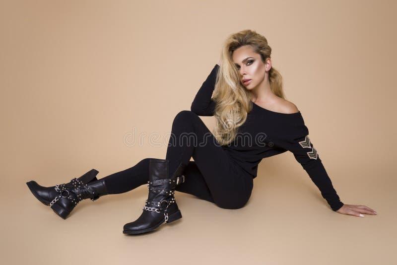Schönes, junges weibliches Modell in einer Herbstwinter-Kleidung, Militärhoodie und Overall und Stiefel auf einem beige Hintergru lizenzfreie stockbilder