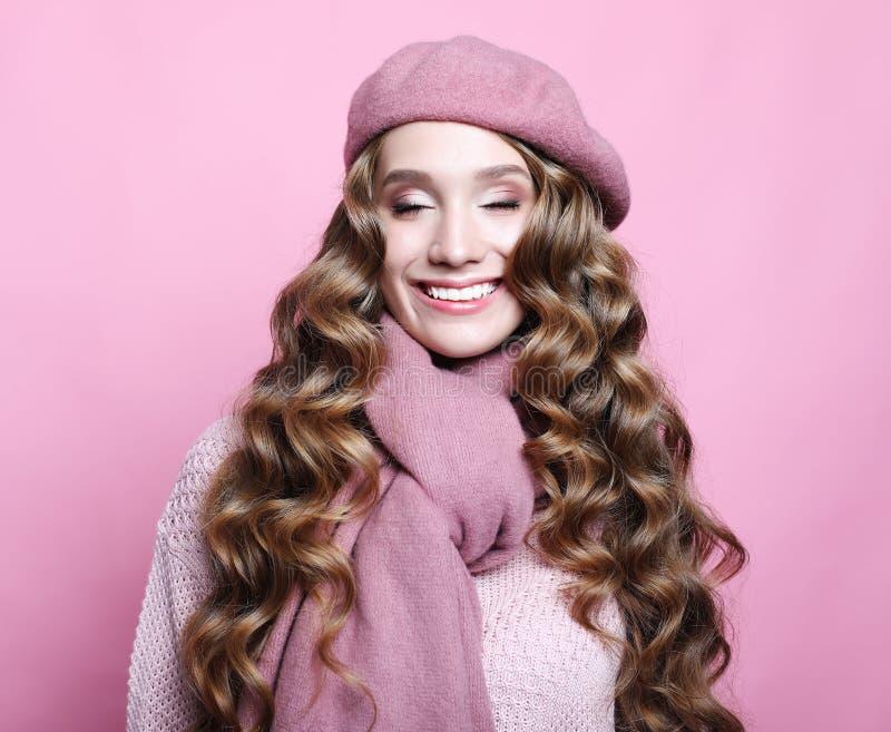 Schönes junges weibliches Modell mit dem langen gewellten Haar, das rosa Barett und Schal trägt lizenzfreie stockbilder