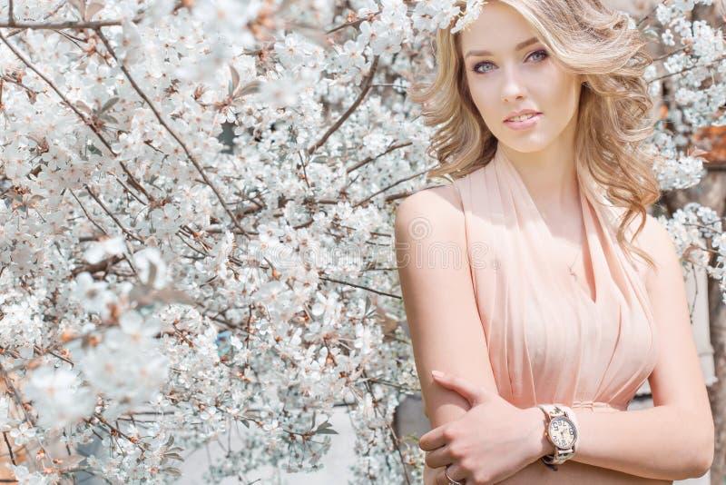 Schönes junges zartes süßes Mädchenfliegen in einem hellen Kleid, das in einen üppigen Kirschgarten geht lizenzfreie stockbilder