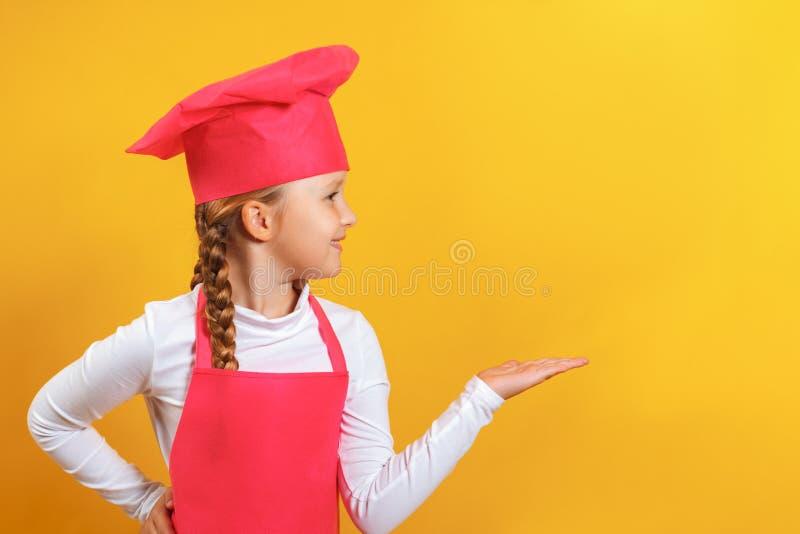 Schönes Küchenchefs kleines Mädchen auf gelbem Hintergrund Das im Profil befindliche Kind zeigt eine Hand an einem leeren Platz lizenzfreie stockfotos