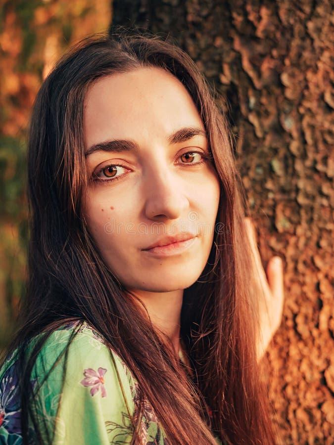 Schönes kaukasisches brunette Mädchen des Porträts mit dem langen Haar im Wald bei Sonnenuntergang lehnte sich an einem Baum Einh stockbild