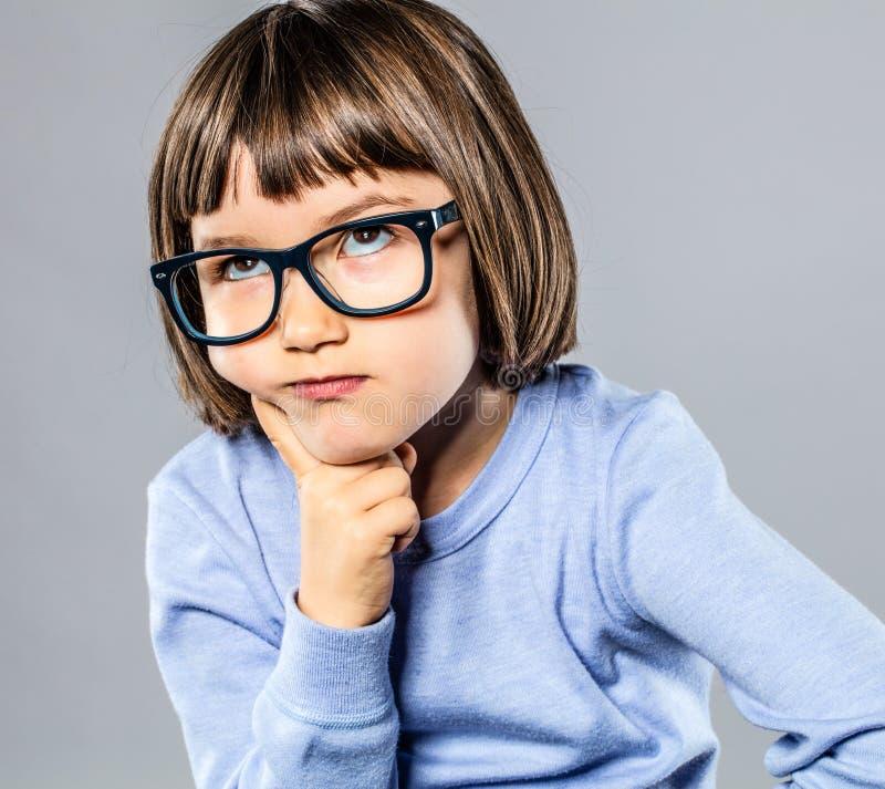 Schönes Kind, das Denker mit ernsten Brillen für intelligente Lösung spielt lizenzfreie stockfotos