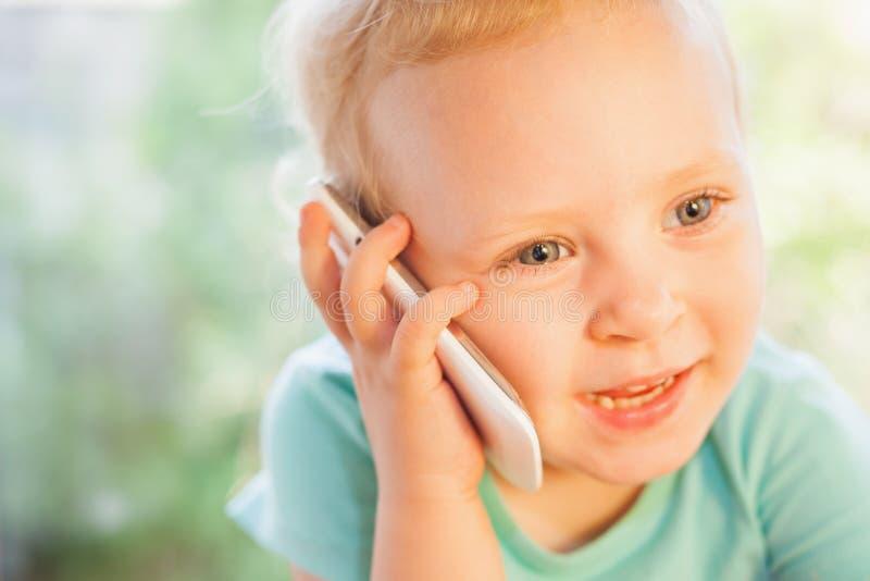 Schönes Kind, das durch Handy mit ihrer Mutter spricht stockbild