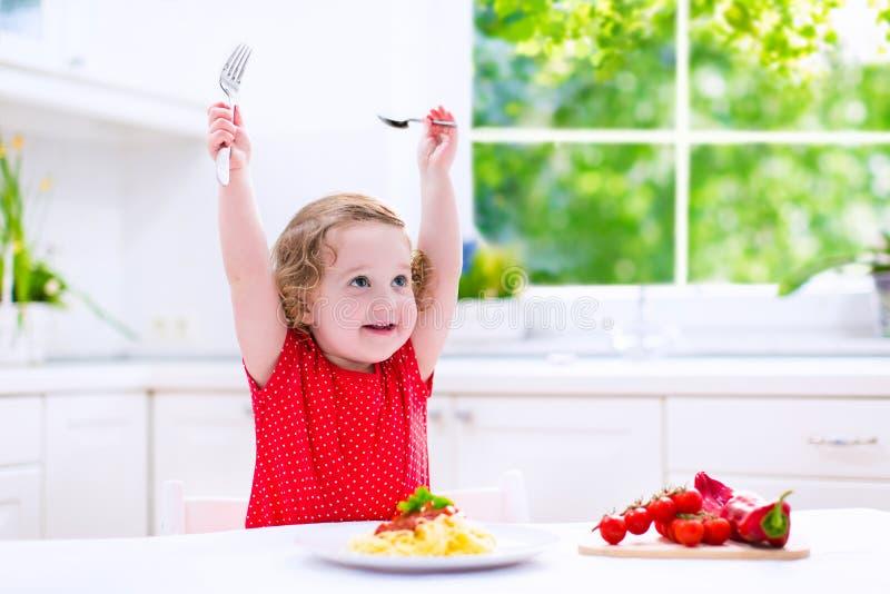 Schönes Kind, das Teigwaren isst lizenzfreies stockfoto