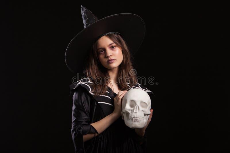 Schönes Kind-dressedup in einem schwarzen Kleid für Halloween-Karneval mit einem menschlichen Schädel in den Händen lizenzfreie stockfotografie