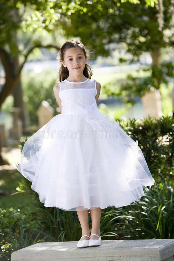 Schönes Kind im weißen Kleid auf Parkbank lizenzfreies stockbild