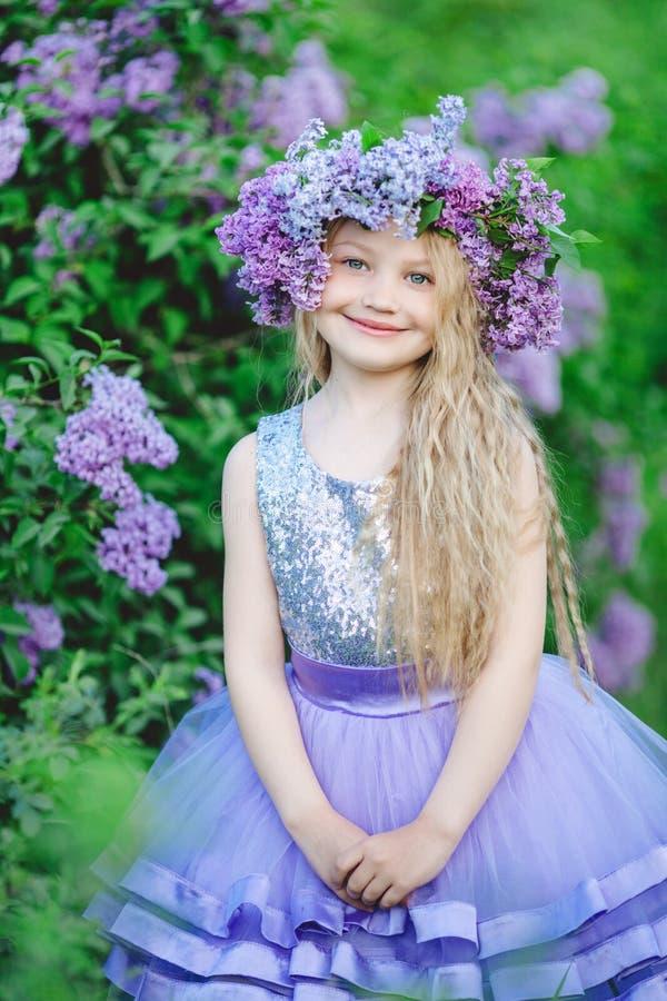 Schönes Kindermädchen mit Kranz von lila Blumen stockfotos