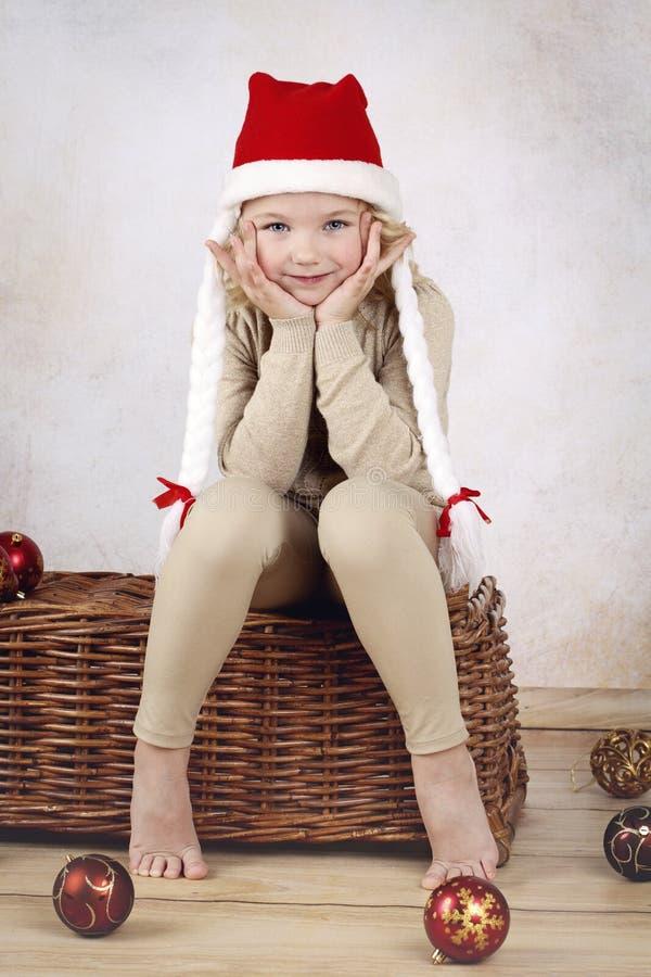 Schönes Kindertragende Weihnachtskappe, die auf Flechtweide sitzt lizenzfreie stockfotografie